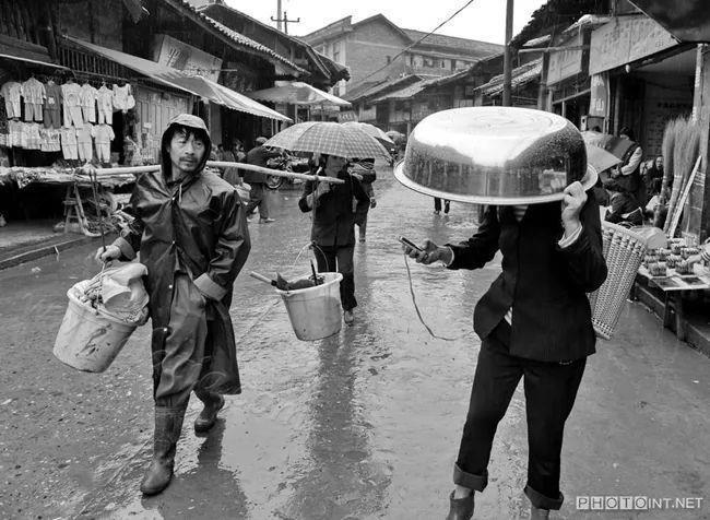 头顶买来的铝盆在雨中接听电话 2010年长乐镇