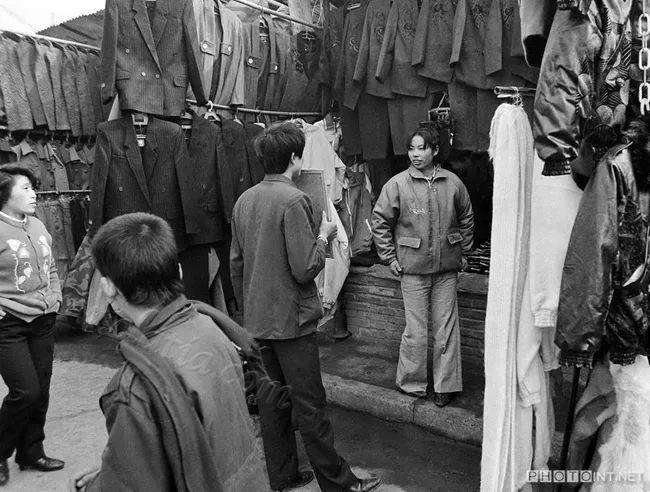 服装摊老板拿着镜子为女顾客试时装 1988年南充市