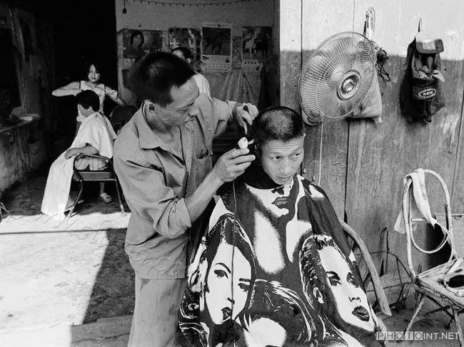 个体理发匠用大美人头像作围裙来招揽客人 2002年长乐镇